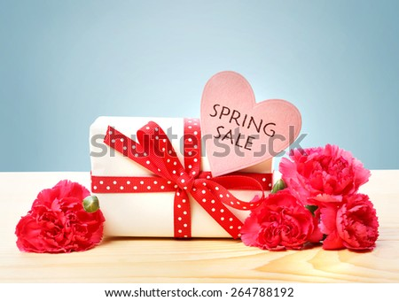 Spring Sale message with gift box and pink carnations - stock photo