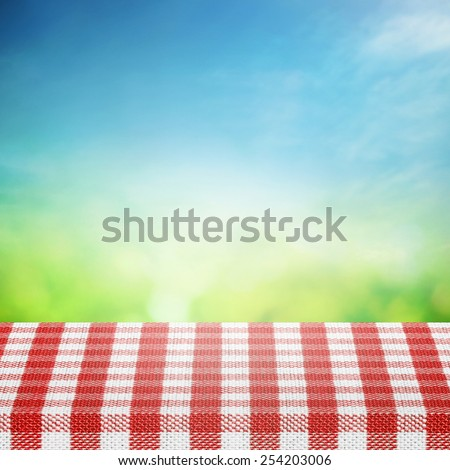 Spring sky with table for picnic in tablecloth  - stock photo