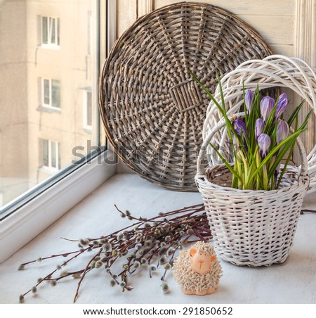 Spring still life with crocus in a decorative bucket  and easter lamb on the window and willow twigs - stock photo