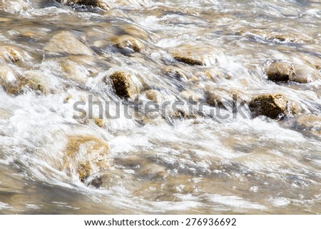 Spring stream flowing through mossy rocks.  Fast shutter speed gives the water flow an abstract painterly look. - stock photo