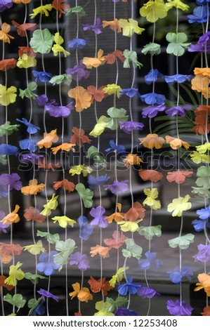 Spring strings: artificial flowers hang like a see-through curtain in a store window - stock photo