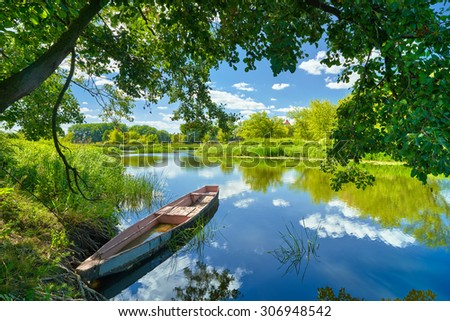 Spring summer landscape blue sky clouds Narew river boat green trees countryside grass Poland water leaves - stock photo