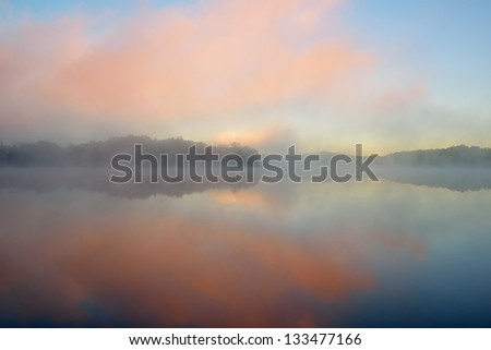 Spring sunrise Whitford Lake in fog, Fort Custer State Park, Michigan, USA - stock photo