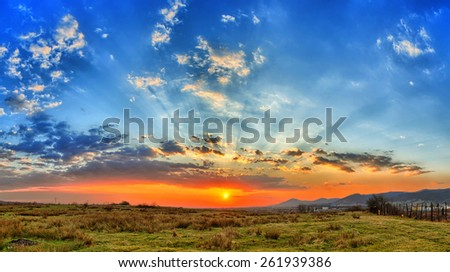 Spring sunset with colored clouds and orange sky - stock photo