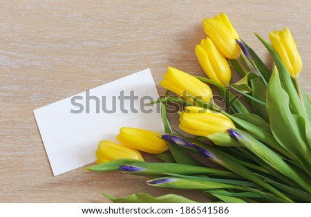 Spring tulips and white paper lying on wood - stock photo