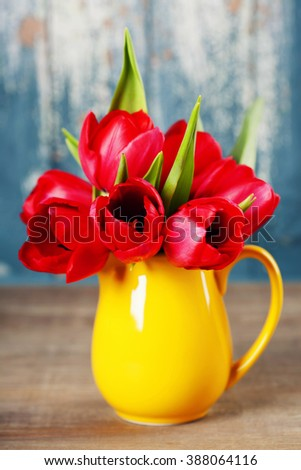 Spring tulips in a vase  on wooden table - spring, easter or gardening concept - stock photo