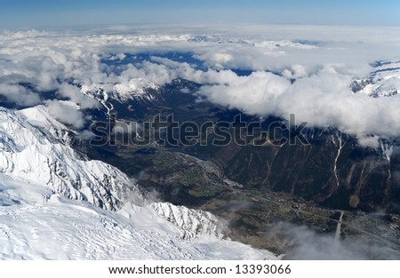 Spring valley Chamonix between high snow mountains occupied by light layer of white clouds and blue sky, view from above - stock photo