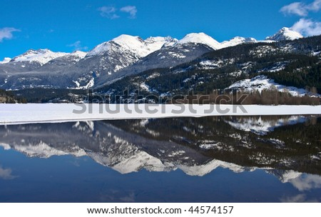 Spring view of the mountains with lake half melted - stock photo