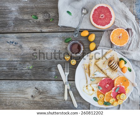 Spring vitamin breakfast set. Thin crepes or pancakes with fresh grapefruit, orange, kumquat, honey, cream and mint leaves over a rustic wood background, top view  - stock photo