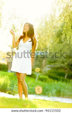 Spring woman in summer dress walking in green park enjoying the sun. Playful and beautiful mixed race girl on warm sunny day. - stock photo