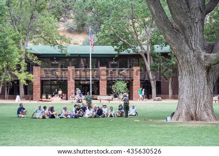 Springdale, UT/USA - circa August 2011: Tourists sitting on the grass and listening to ranger lecture in Zion National Park in Utah