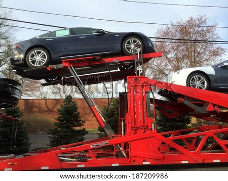 SPRINGFIELD, NJ - APRIL 14: New Model S cars lie on a truck outside a Tesla Service facility on April 14, 2014 in Springfield, NJ. On March 11th, NJ passed new rules banning direct-to-consumer sales. - stock photo
