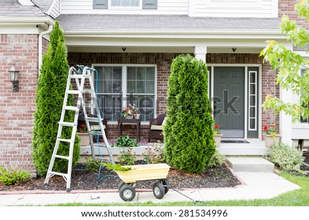 Springtime trimming of Arborvitae or ornamental evergreen Thuja trees growing in a flowerbed in front of a house using a stepladder, trimmer and small yellow cart to remove debris and foliage - stock photo