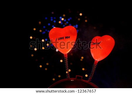 springy hearts atop someone's head with fireworks at the background - stock photo
