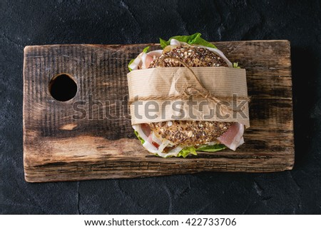 Sprinkle seeds Whole Grain bagel with fried onion, green salad and prosciutto ham on wood chopping board over black stone textured background. Top view - stock photo
