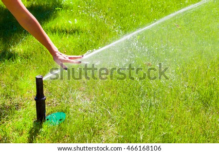 sprinkler head dispersing water on grass.female hand touches the water jet