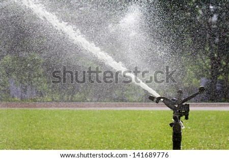 sprinkler head watering the sport lawn - stock photo