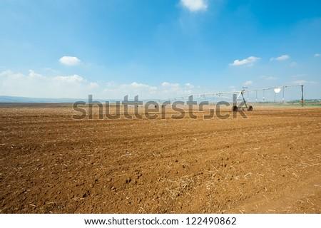 Sprinkler Irrigation on a Plowed Field in Israel - stock photo