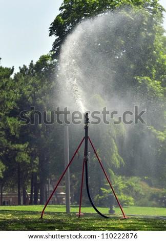 Sprinkler spraying water at the park - stock photo