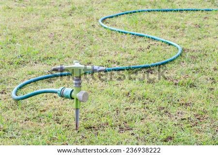 Sprinkler water on grass field - stock photo