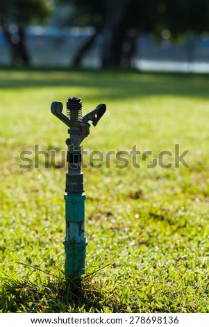 Sprinkler watering lawns during the early morning hours of the day. - stock photo