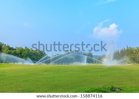 sprinklers on golf course at mae mo mine - stock photo