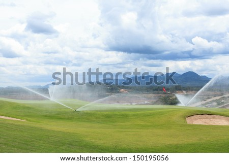 sprinklers on golf course at mae-moe mine - stock photo