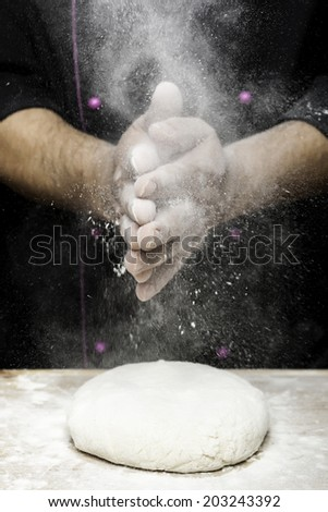sprinkling flour with hands on bread dough - stock photo