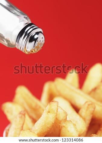 sprinkling salt on chips against red background - stock photo