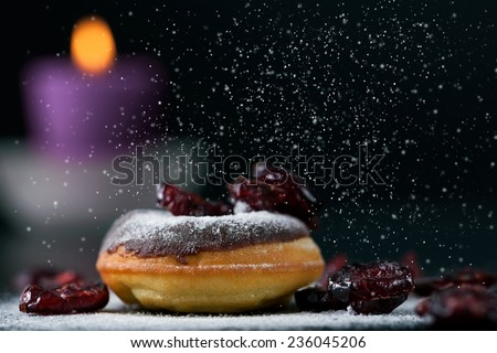 Sprinkling sugar on delicious donut topped with chocolate and cranberries. Romantic atmosphere, candle in background. Shallow depth of field. - stock photo