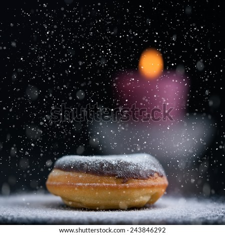 Sprinkling sugar on delicious donut topped with chocolate. Romantic atmosphere with candle in background. Shallow depth of field. - stock photo