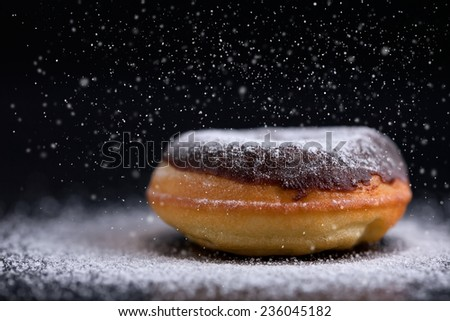 Sprinkling sugar on delicious donut topped with chocolate. Shallow depth of field. - stock photo