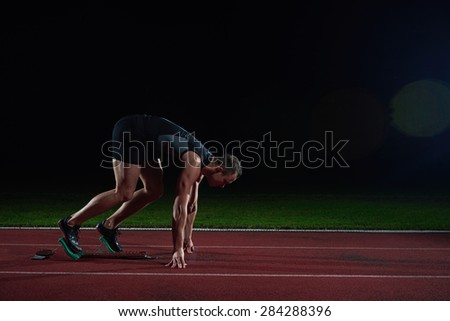 Sprinter leaving starting blocks on the running track. Explosive start. - stock photo