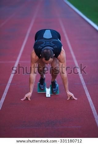 Sprinter leaving starting blocks on the running track. Explosive start. - stock photo