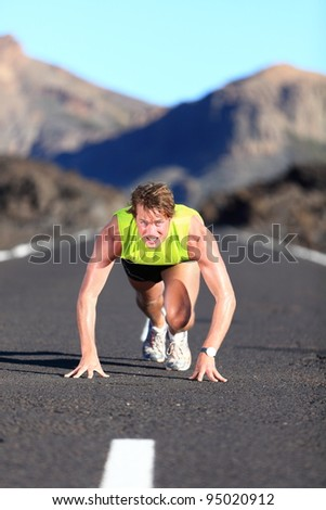 Sprinter ready for sprint. Man runner starting running sprint on road in beautiful mountain nature landscape. Fit Caucasian male fitness model during work out. - stock photo