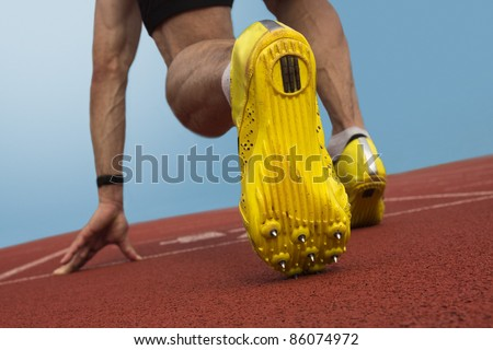 Sprinter with spikes is in start position - stock photo