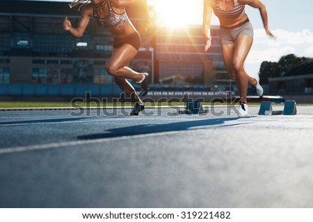 Sprinters starts out of the blocks on athletics racetrack with bright sunlight. Low section shot of female athletes starting a race in stadium with sunflare. - stock photo