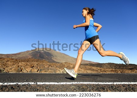 Sprinting running woman - female runner training outdoors jogging on mountain road in amazing landscape nature. Fit beautiful fitness model working out for marathon outside in summer. - stock photo