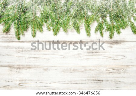 Spruce sprigs with snow on bright wooden texture. Christmas background - stock photo