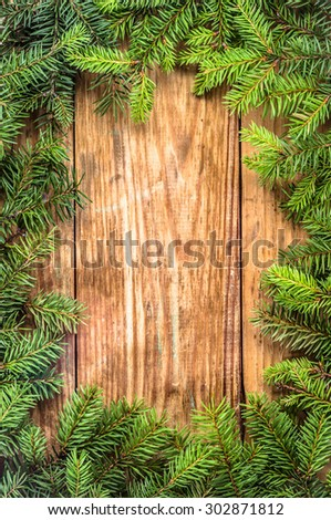 Spruce twigs on a wooden background useful as christmas background in vintage style. Arrangement in frame pattern. Photo made in vertical orientation. - stock photo