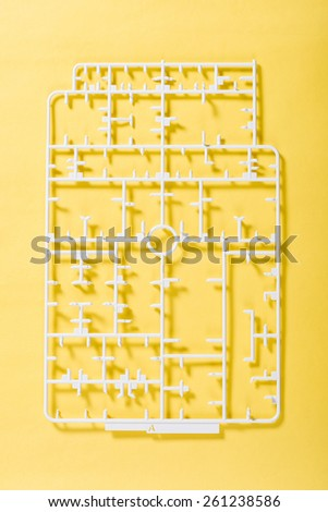 sprue or injection moulding of toy on yellow background - stock photo