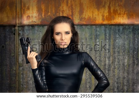Spy Agent Woman in Black Leather Suit Holding Gun - Portrait of a cool super heroine in action  - stock photo