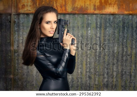Spy Agent Woman in Black Leather Suit Holding Gun - Portrait of a super heroine in action  - stock photo