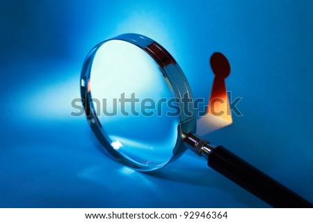 Spying concept. Magnifying glass near keyhole with beam of light - stock photo