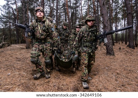 Squad of soldiers evacuating wounded trooper from battlefield - stock photo