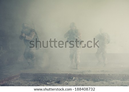Squad of US marines in action in ruined building - stock photo
