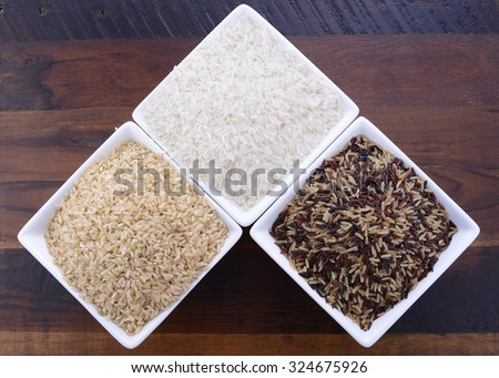 Square bowls of uncooked brown, white, and red and black rice on dark wood vintage background, overhead view.  - stock photo