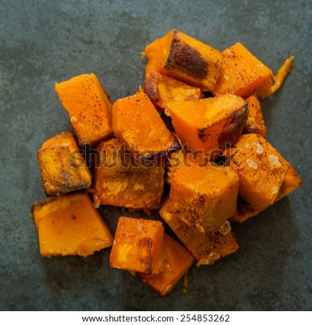 Square crop of Roasted pumpkin on a black slate background - stock photo