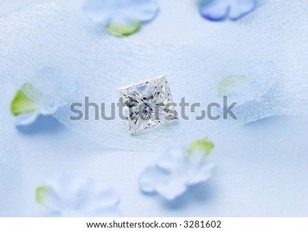 Square Diamond with silk flowers on blue - stock photo