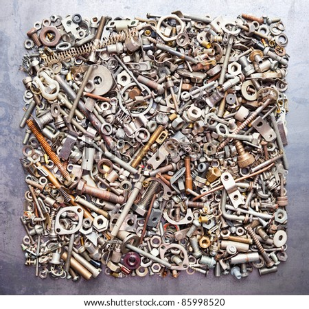 Square from assorted nuts and bolts on metal texture background